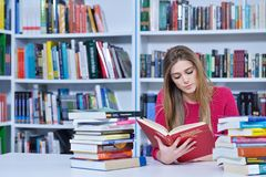 Beautiful female student in a university library. Group of students learning in library at university royalty free stock photography