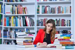 Beautiful female student in a university library. Group of students learning in library at university royalty free stock image