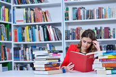 Beautiful female student in a university library. Group of students learning in library at university stock image