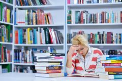 Beautiful female student in a university library. Group of students learning in library at university royalty free stock photos