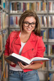 Beautiful Female Student In A University Library. A Portrait Of An Caucasian College Student Girl In Library - Shallow Depth Of Field royalty free stock image