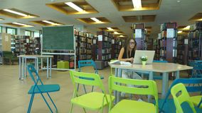 Beautiful female student in a university library stock video footage