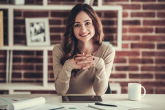 Beautiful female student. Beautiful young female student is looking at camera and smiling while sitting at desk at home royalty free stock images