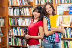 Beautiful female students in a library Stock Photography