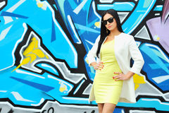 Beautiful female in sunglasses. Near grafitty wall royalty free stock image