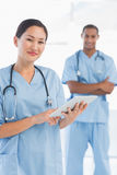 Beautiful female surgeon holding digital tablet Stock Image
