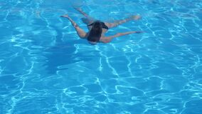 Beautiful female in a swimsuit is floating under blue clear water in poolside into summer holiday stock video