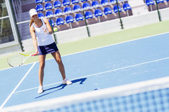 Beautiful female tennis player in action Stock Images