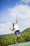 Beautiful female tennis player serving Royalty Free Stock Photography