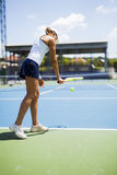 Beautiful female tennis player serving Royalty Free Stock Photo
