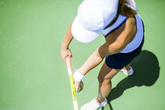 Beautiful female tennis player serving Stock Image
