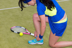 Beautiful female tennis player tying shoelaces Stock Photography