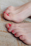 Beautiful female toes with pedicure. On beige carpet Royalty Free Stock Images