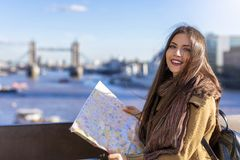 Female tourist looks at the street map in front of the Tower Bridge, UK royalty free stock photography