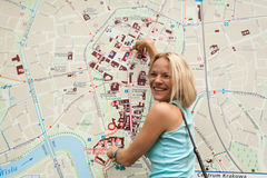 A beautiful female tourist searching a place on the map stock images