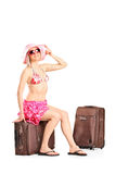 Beautiful female tourist sitting on her luggage Stock Image