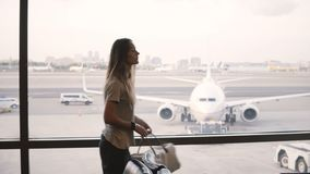 Beautiful female tourist stands at airport lounge terminal window looking at airplanes, then takes the bag and leaves. Attractive serious Caucasian stock video