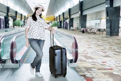 Beautiful female tourist wearing with suitcase in an airport. Beautiful female tourist wearing hat with suitcase at an airport Royalty Free Stock Images