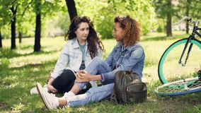 Beautiful female tourists friends in denim clothing are having rest after riding bikes, girls are sitting on grass in stock footage