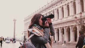 Beautiful female travel blogger with camera taking photos of St Mark buildings in Venice Italy, smiling slow motion. Professional journalist enjoying traveling stock footage