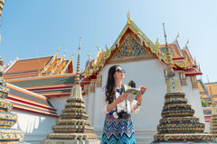 Beautiful female traveler holding guidebook. Friendly beautiful female traveler holding guidebook reading travel information standing on wat pho temple and stock photography