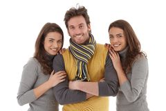 Beautiful female twins embracing handsome man Stock Photos