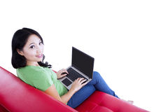 Beautiful female typing on red sofa - isolated Royalty Free Stock Photos