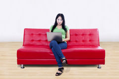 Beautiful female using laptop on red sofa at home Royalty Free Stock Images
