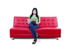 Beautiful female using laptop on red sofa - isolated Royalty Free Stock Image