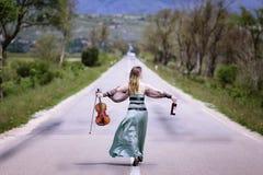 Beautiful female viola player walking along the highway royalty free stock image