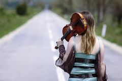 Beautiful female viola player walking along the highway stock photography