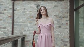 Beautiful female violinist walks at luxury house with violin in hand stock video