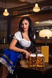 Beautiful female waitress wearing traditional dirndl and holding huge beers in a pub. Stock Photo
