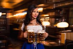 Beautiful female waitress wearing traditional dirndl and holding huge beers in a pub. Royalty Free Stock Images