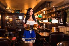 Beautiful female waitress wearing traditional dirndl and holding huge beers in a pub. Royalty Free Stock Image