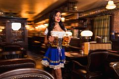 Beautiful female waitress wearing traditional dirndl and holding huge beers in a pub. Brunette carries two glasses of beer between the tables in the bar stock image