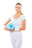 Beautiful female wearing  sports clothes holdin blue yoga mat an Stock Images