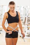 Beautiful female wearing sports clothes measuring waist Royalty Free Stock Photography