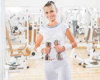 Beautiful female with weights in gym Stock Photos