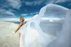Beautiful female with white flag on a beach Stock Photography
