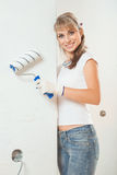 Beautiful female worker holding paintroller near the wall. Beautiful young woman Royalty Free Stock Photography