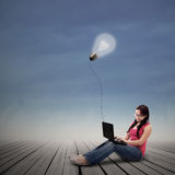Beautiful female working on laptop under lit bulb outdoor Royalty Free Stock Photography