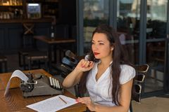Female writer with vintage typewriter making notes in a coffee s. Beautiful female writer with long brown hair wearing white shirt and red lipstick, taking notes stock photography