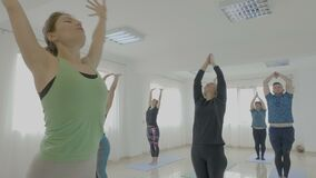 Beautiful female yoga trainer teaching her class made of regular people new stretching poses in a bright studio -. Beautiful female yoga trainer teaching her stock video footage
