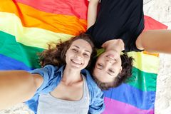 Beautiful female young lesbian couple in love makes selfie lying on the background of the rainbow flag, symbol of the community, stock photos