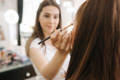 Beautiful femalemakeup artist doing makeup for a young redhead girl in a beauty salon sitting in front of a large mirror royalty free stock images