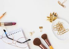 Beautiful feminine accessories in gold color on the white table. Royalty Free Stock Photo