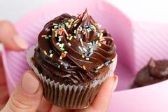 Beautiful feminine hand holding tasty appetizing chocolate cupcake. Pink Gift Box. Closeup. royalty free stock photography