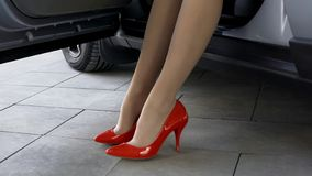 Beautiful feminine model in red high-heeled shoes sitting on driver seat in car. Stock photo royalty free stock photos