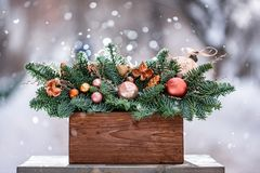 Beautiful festive arrangement of fresh spruce with ball toys in a rustic wooden box. Christmas mood. It snows in winter. Beautiful festive arrangement of fresh royalty free stock photography